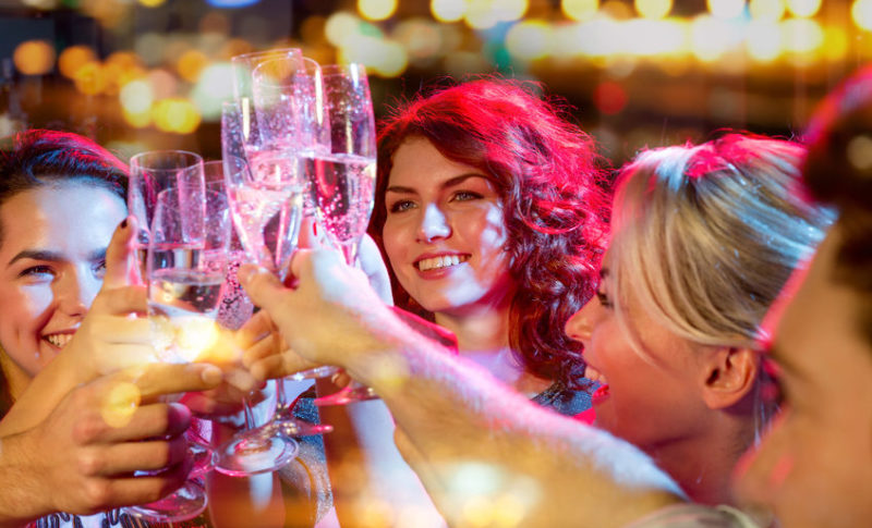 48507564 - party, holidays, celebration, nightlife and people concept - smiling friends with glasses of champagne in club